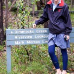 Rosie pointing to a sign that says Dimmocks Creek