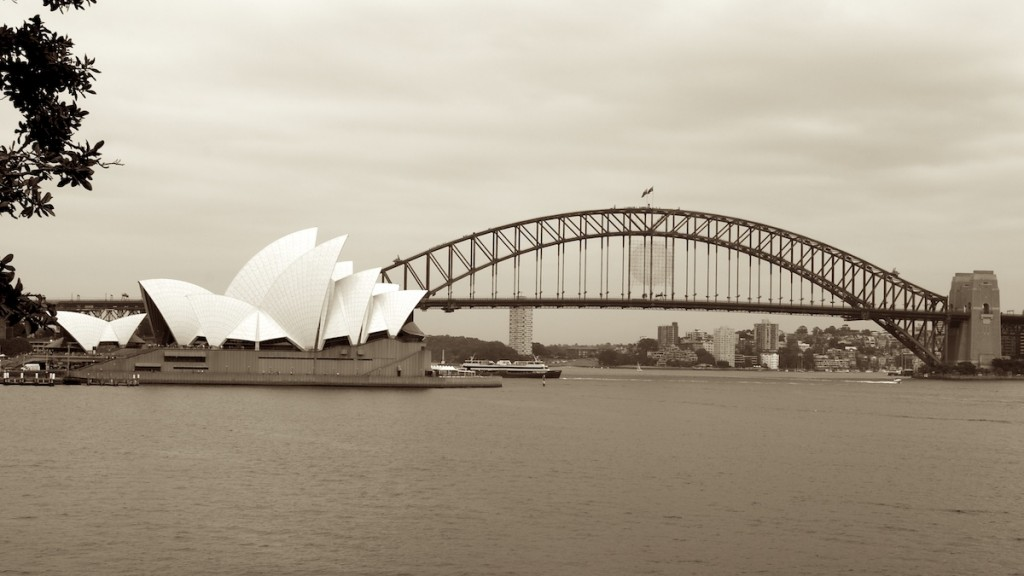 The opera house and harbour bridge with a ferry passing underneath.